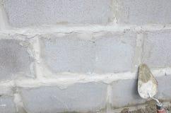 Лопатка на предпосылке серого цвета cinderblock На фоне кирпичной кладки лопатка Стоковая Фотография