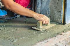 Лопатка пользы работника каменщика, который нужно приглаживать или выравнивать жидкостный бетон  стоковые изображения rf