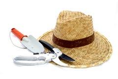 Лопатка соломенной шляпы и руки и подрезая ножницы на белизне стоковое изображение rf