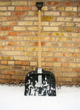 Лопаткоулавливатель снега в снеге на предпосылке кирпичной стены Стоковые Изображения RF