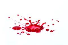 Лоснистые красные жидкостные капельки (splatters) изолированные на белизне стоковое фото rf