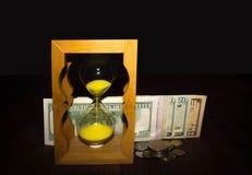 Лоснистые прежние часы стоя с американскими долларовыми банкнотами Стоковое фото RF