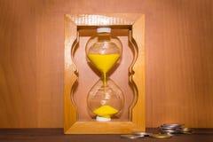 Лоснистые прежние часы стоя с монетки Стоковые Фото