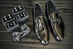 Лоснистые черные ботинки, кнопки рубашки на комплекте коробки, черная бабочка на черном деревянном поле - взгляд сверху, закрытое стоковая фотография