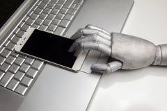 Лоснистый smartphone при рука робота касаясь ему пальцем на компьтер-книжке Стоковые Изображения RF