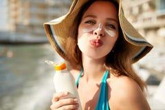 Лосьон Suntan Милая женщина прикладывая солнцезащитный крем suntan cream солнечный от бутылки пластмасового контейнера на ее носе Стоковое Фото