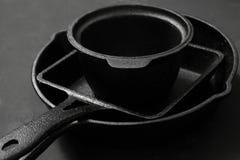 Лотки и бак литого железа на черной деревянной предпосылке Стоковые Фото