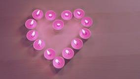 Лотки камеры через горящие свечи помещенные в сердце формируют сток-видео