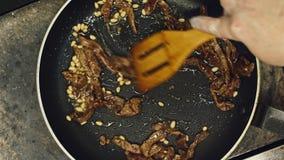 Лоток кашевара жарит мясо Человек жарит мясо на горящей сковороде Огонь на сковороде конец вверх Жарка мяса сток-видео