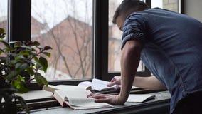 ЛОТОК молодого человека говорит на телефоне пока изучающ стоять около окна акции видеоматериалы