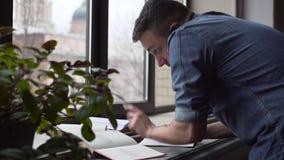 ЛОТОК молодого человека получает помощь в учить телефоном стоя около окна видеоматериал