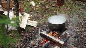 Лоток с кипя супом над лагерным костером в внешнем сток-видео