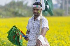 Лоточница продает бангладешские национальные флаги на поле мустарда на Munshigonj, Дакке, Бангладеше стоковые фото