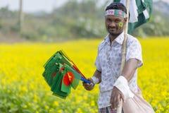 Лоточница продает бангладешские национальные флаги на поле мустарда на Munshigonj, Дакке, Бангладеше стоковая фотография rf