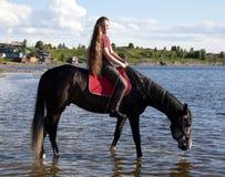 лошадь девушки водит для того чтобы намочить Стоковая Фотография