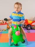 Лошадь игрушки счастливого мальчика Llittle скача стоковые фото