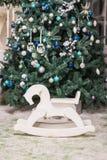 Лошадь игрушки ` s детей тряся около рождественской елки Подарки и концепция праздников кресло-качалка лошади для детей Деревянны стоковая фотография