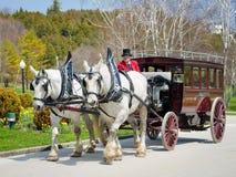 Лошад-нарисованный винтажный экипаж транспортирует гостей к грандиозной гостинице Стоковое фото RF