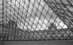 Лувр через стеклянную пирамиду решетки стоковое фото