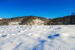 Луг покрытый с снегом в горах в зиме Стоковое фото RF
