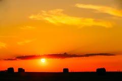 Луг поля лета с силуэтами связок сена под заходом солнца Sunl Стоковые Изображения RF