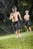 лужайка мальчиков играя спринклер Стоковое Изображение RF