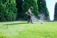 Лужайка работника кося в саде стоковые изображения