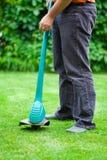 Лужайка человека кося с триммером травы Стоковая Фотография