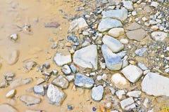 Лужица на скалистой земле - фоновом изображении Стоковое Фото