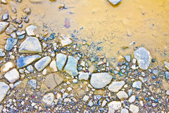 Лужица на скалистой земле - фоновом изображении Стоковые Изображения