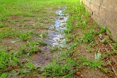Лужицы после дождя около стены деревянного дома Стоковые Изображения RF