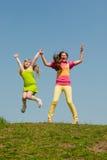 лужок 2 девушок зеленый скача Стоковые Изображения RF