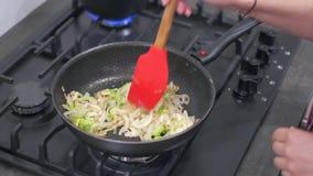 Луки женщины смешивая и зеленый перец в горячем лотке сток-видео