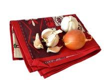 Луки и чеснок на красном полотенце Стоковые Фото