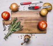 Луки, томаты, пук розмаринового масла, картошек, ножа для очищая картошек, точильщика перца вывешенного вокруг разделочной доски Стоковые Изображения