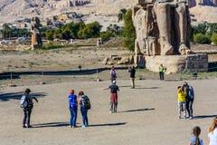 Луксор, Египет - 11-ое декабря 2018: Туристы принимая фото статуй колоссов Memnon фараона Amenhotep III в Луксоре, Египте стоковые фотографии rf