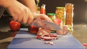 Лук отрезка рук кашевара крупного плана с ножом на кухонном столе сток-видео
