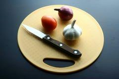 Лук, чеснок, томат и нож на прерывая доске Стоковое фото RF
