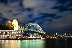 Лунатируйте освещенный мост гавани Сидней с moving облаками в небе Стоковое Изображение RF
