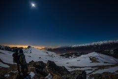 Луна и звёздное небо, снег на Альпах, рыбий глаз Созвездие, бетельгейзе и Sirio Ориона Долгая выдержка запачкала 2 hikers l Стоковые Фотографии RF