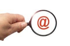 Лупа в знаке руки и электронной почты на белой предпосылке стоковые изображения