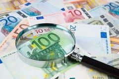 Лупа на деньгах евро стоковые изображения