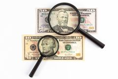 Лупа помещенная на счетах доллара США стоковое фото rf