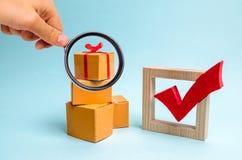 Лупа смотрит подарочную коробку на куче коробок и красной контрольной пометки концепция обнаружения идеального подарка Шоппинг стоковое фото