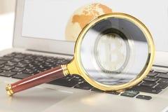 Лупа с bitcoin внутрь на компьтер-книжке с глобусом земли на экране Стоковое Фото