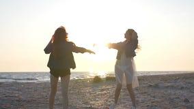 Лучи захода солнца над морем освещают танец на пляже 2 молодых сексуальных женщин одетых в стиле boho видеоматериал