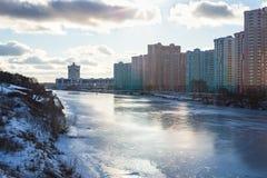 Лучи солнечного света освещают крыши небоскребов стоя на банке замороженного реки Стоковое фото RF