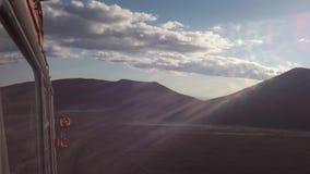 Лучи солнца светят в камере вдоль дороги на старых полях лавы на наклонах видео отснятого видеоматериала запаса Tolbachik вулкано акции видеоматериалы
