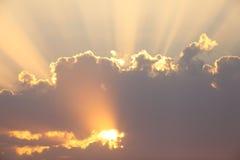 Лучи Солнця через облака на заходе солнца Стоковые Изображения