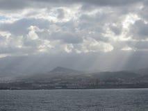 Лучи через облака для того чтобы сделать остров посветить Стоковые Изображения RF
